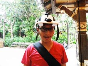 suami lagi nyoba topi baru di gerobak souvenir