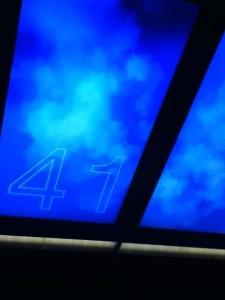bagian atas lift nya didesain seperti langit biru berawan,, dengan angka-angkayang berubah dengan cepat,,yes yes angka-angka itu adalah angka lantai yang sedang kita lewati